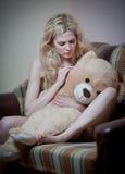 Junge blonde sinnliche Frau, die auf dem Sofa sich entspannt mit einem enormen Teddybären sitzt Lizenzfreies Stockbild