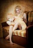 Junge blonde sinnliche Frau, die auf dem Sofa sich entspannt mit einem enormen Teddybären sitzt Stockbild