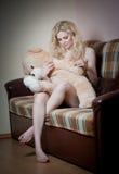 Junge blonde sinnliche Frau, die auf dem Sofa sich entspannt mit einem enormen Teddybären sitzt Lizenzfreie Stockfotos