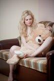Junge blonde sinnliche Frau, die auf dem Sofa sich entspannt mit einem enormen Teddybären sitzt Stockbilder