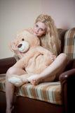 Junge blonde sinnliche Frau, die auf dem Sofa sich entspannt mit einem enormen Teddybären sitzt Stockfoto