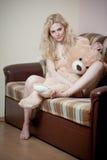 Junge blonde sinnliche Frau, die auf dem Sofa sich entspannt mit einem enormen Teddybären sitzt Stockfotografie