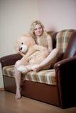 Junge blonde sinnliche Frau, die auf dem Sofa sich entspannt mit einem enormen Teddybären sitzt Lizenzfreies Stockfoto