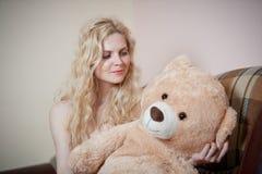 Junge blonde sinnliche Frau, die auf dem Sofa sich entspannt mit einem enormen Teddybären sitzt Stockfotos