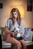 Junge blonde sinnliche Frau, die auf dem Stuhl sich entspannt mit einem Pandabärnspielzeug sitzt. Schönes junges Mädchen mit der b Stockfotos