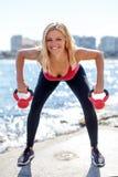 Junge blonde sportliche Frau, die kettlebells hält Stockbild