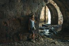 Junge blonde touristische Frau, die in der alten Steinwerft stading und das Meer in der alten Stadt, Alanya, die Türkei betrachte Lizenzfreie Stockfotografie