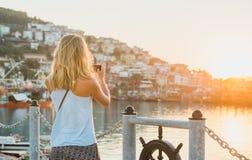 Junge blonde touristische Frau, die Foto vom Sonnenuntergang, Alanya, die Türkei macht Stockfotografie