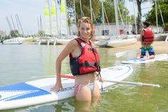 Junge blonde weibliche Aufstellung gegen paddleboard auf See Lizenzfreie Stockbilder