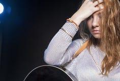 Junge blonde weibliche Aufstellung mit Gitarre gegen Schwarzes Stockfotografie