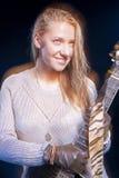Junge blonde weibliche Aufstellung mit Gitarre gegen Schwarzes Kombination des Blitzes und des Halogens benutzt Stockbild