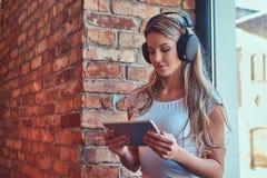 Junge blonde weibliche hörende Musik und Anwendung einer digitalen Tablette beim Sitzen auf einem Fensterbrett in einem Raum mit  Stockbilder