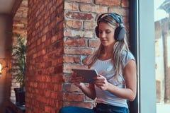 Junge blonde weibliche hörende Musik und Anwendung einer digitalen Tablette beim Sitzen auf einem Fensterbrett in einem Raum mit  Lizenzfreies Stockbild