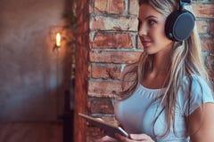 Junge blonde weibliche hörende Musik und Griffe eine digitale Tablette beim Sitzen auf einem Fensterbrett in einem Raum mit Dachb Stockfoto