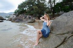 Junge blonde weibliche Person, die auf Sand nahe Meer und Steinen sitzt, durch Smartphone spricht und sich Daumen zeigt Stockfoto