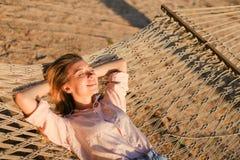 Junge blonde weibliche Person, die barfuß auf Sand in der Flechtweide liegt Stockbild