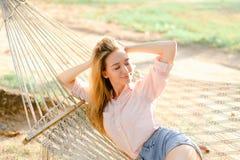 Junge blonde weibliche Person, die in der weißen Weidenhängematte auf Sand, tragende kurze Jeanshose liegt Stockfoto
