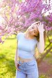 Junge blonde weibliche Person, die im Park mit Blütenhintergrund steht Lizenzfreies Stockfoto