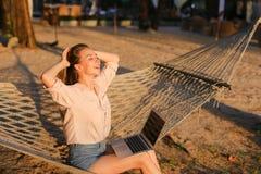 Junge blonde weibliche Person, die mit Laptop arbeitet und auf Sand in der Weidenhängematte sitzt Stockfoto