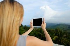 Junge blonde weibliche Person, die Tablette verwendet und Fotos in Gebirgshintergrund macht Stockbild