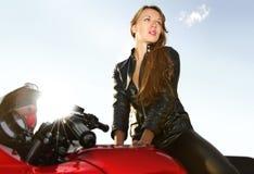 Junge Blondine auf einem großen roten Motorrad stockbild