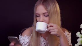 Junge Blondine auf einem schwarzen Hintergrund Sie trinkt ihren Kaffee und liest eine Textnachricht auf ihrem Smartphone stock footage