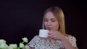 Junge Blondine auf einem schwarzen Hintergrund Sie trinkt ihren Kaffee und schaut träumerisch stock footage