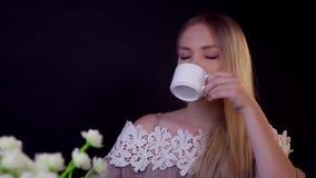 Junge Blondine auf einem schwarzen Hintergrund Sie trinkt ihren Kaffee und schaut träumerisch stock video
