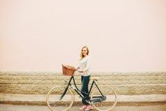 Junge Blondine auf einem Weinlesefahrrad Stockfoto
