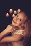 Junge Blondine auf schwarzen Blättern mit candels im Hintergrund Lizenzfreies Stockbild