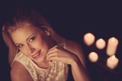 Junge Blondine auf schwarzen Blättern mit candels im Hintergrund Stockfotografie
