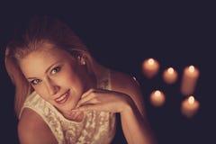Junge Blondine auf schwarzen Blättern mit candels im Hintergrund Lizenzfreie Stockfotos
