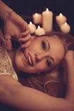 Junge Blondine auf schwarzen Blättern mit candels im Hintergrund Stockfoto