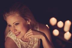 Junge Blondine auf schwarzen Blättern mit candels im Hintergrund Lizenzfreies Stockfoto