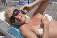 Junge Blondine in den Sonnenbrillen spricht durch Telefon Stockbilder