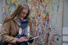 Junge Blondine, die auf Bank und dem Schreiben stationieren stockbilder