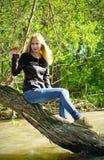 Junge Blondine, die auf getrocknetem-oben Baum sitzen Lizenzfreie Stockbilder