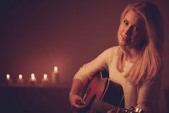 Junge Blondine, die Gitarre im Kerzenlicht spielen Stockfotografie