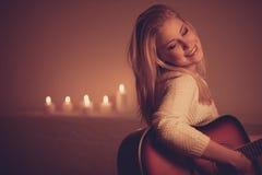 Junge Blondine, die Gitarre im Kerzenlicht spielen Lizenzfreie Stockfotos