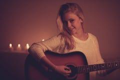 Junge Blondine, die Gitarre im Kerzenlicht spielen Lizenzfreie Stockbilder