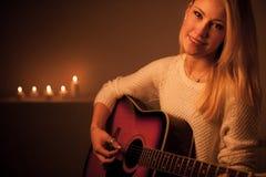 Junge Blondine, die Gitarre im Kerzenlicht spielen Stockbilder