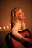 Junge Blondine, die Gitarre im Kerzenlicht spielen Stockbild