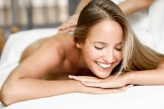 Junge Blondine, die Massage haben und im Badekurort lächeln Lizenzfreie Stockfotografie