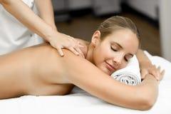 Junge Blondine, die Massage haben und im Badekurort lächeln Lizenzfreies Stockbild