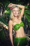 Junge Blondine, die mit Bananenblättern aufwerfen Stockbilder