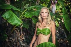 Junge Blondine, die mit Bananenblättern aufwerfen Stockbild