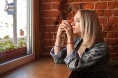 Junge Blondine, die orange Papierschale mit dem Cocktailstroh träumerisch sitzt nahe Fenster gegen Wand des roten Backsteins am C Lizenzfreies Stockbild