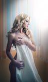 Junge Blondine eingewickelt in der weißen Tuchaufstellung entspannt. Schöne junge Frau mit einem Tuch um ihren Körper nach Bad. Se Stockfotografie