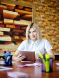 Junge Blondine im Büro, das hinter der Tablette arbeitet Stockbilder