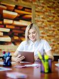 Junge Blondine im Büro, das hinter der Tablette arbeitet Stockfotos